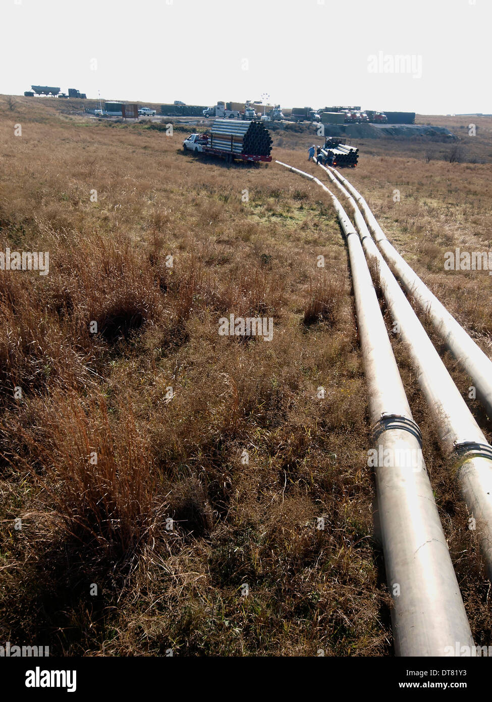 Pipeline brings fresh water to a drilling site to let thousands of gallons get pumped into a well by hydraulic fracturing - Stock Image