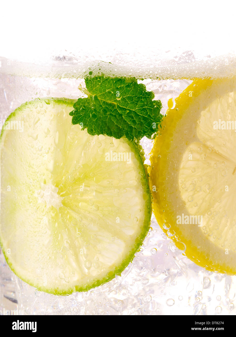 A close up detail of a lemon lime soda with a mint leaf with ice in a clear glass Stock Photo
