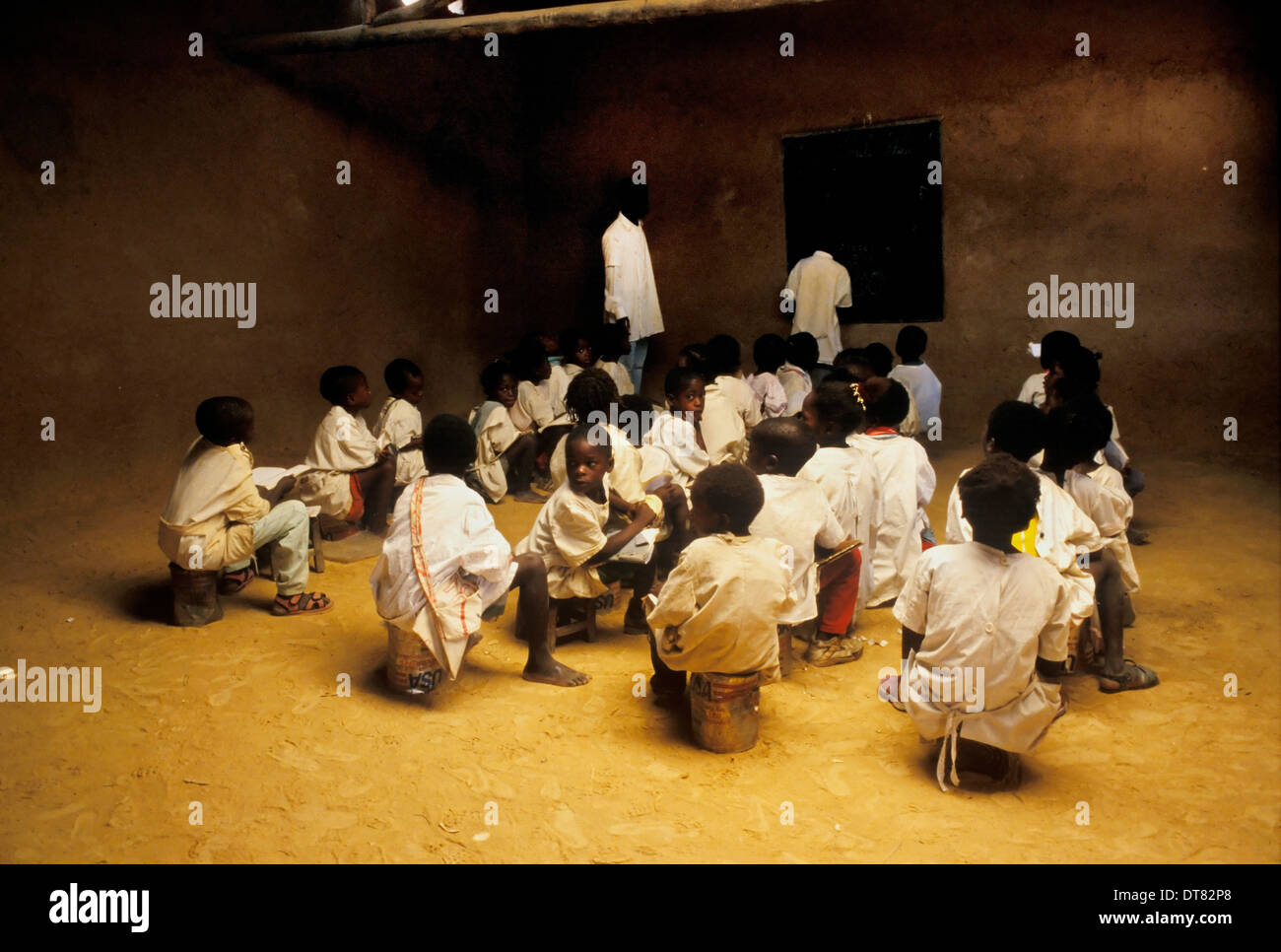 A group of children attending school using as seats U.S. humanitarian aid cans. - Stock Image