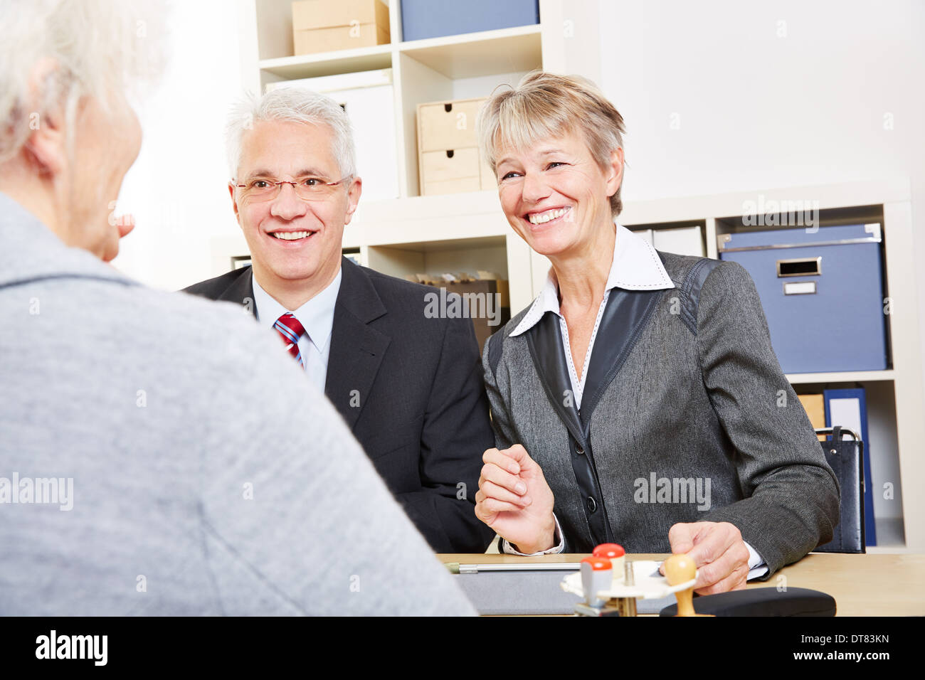 Two elderly business people talking about finances with senior woman - Stock Image
