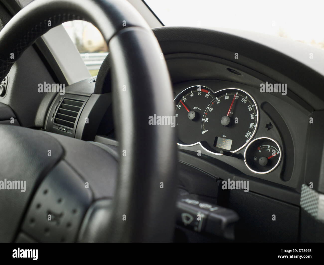 Car dashboard when driving the exact speed limit of 100 kilometers per hour - Stock Image