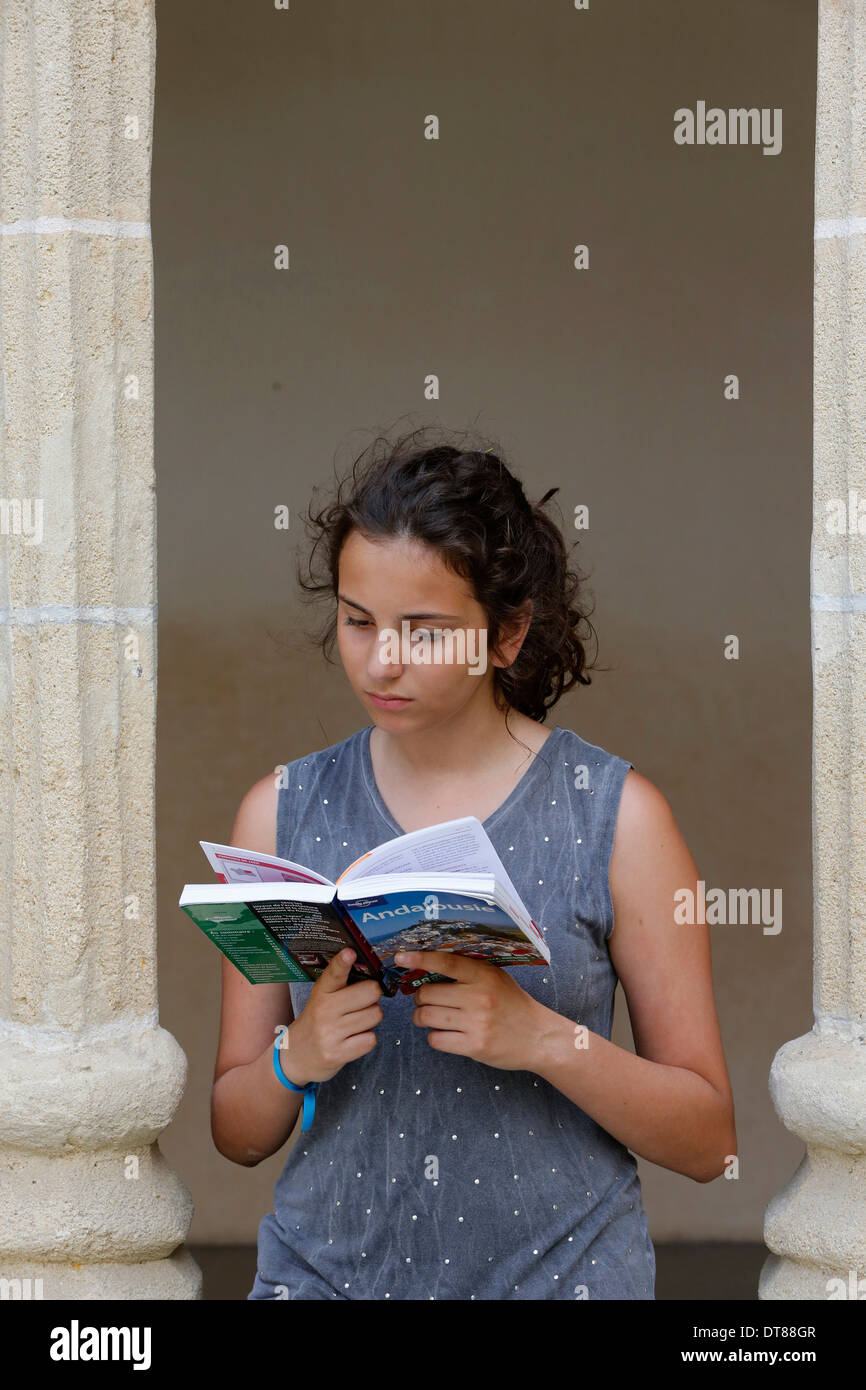 Teenager reading a guidebook - Stock Image