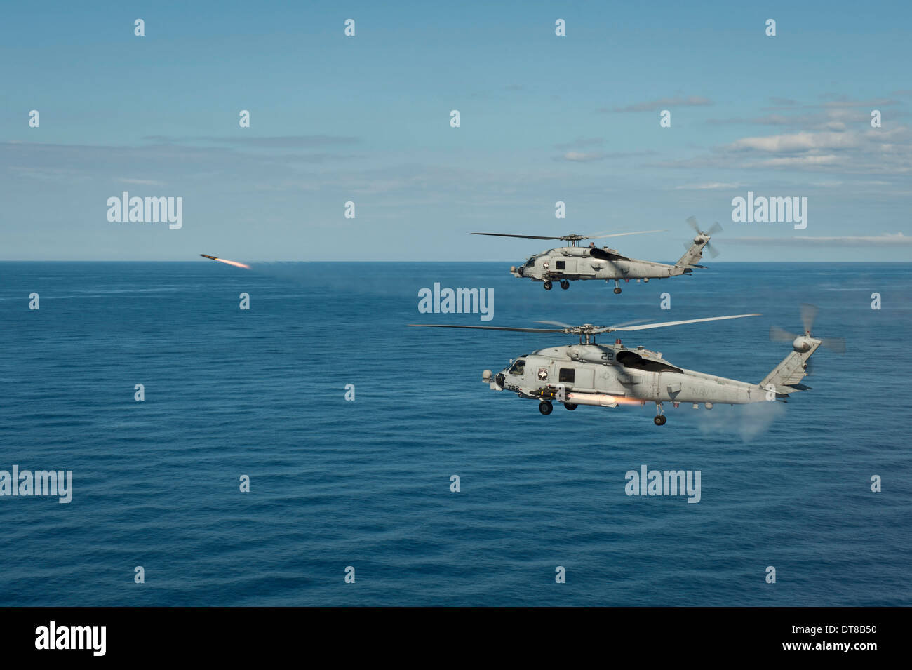 South China Sea, May 18, 2013 - Two MH-60R Sea Hawk helicopters launch AGM-114 hellfire missiles during a live fire exercise. - Stock Image