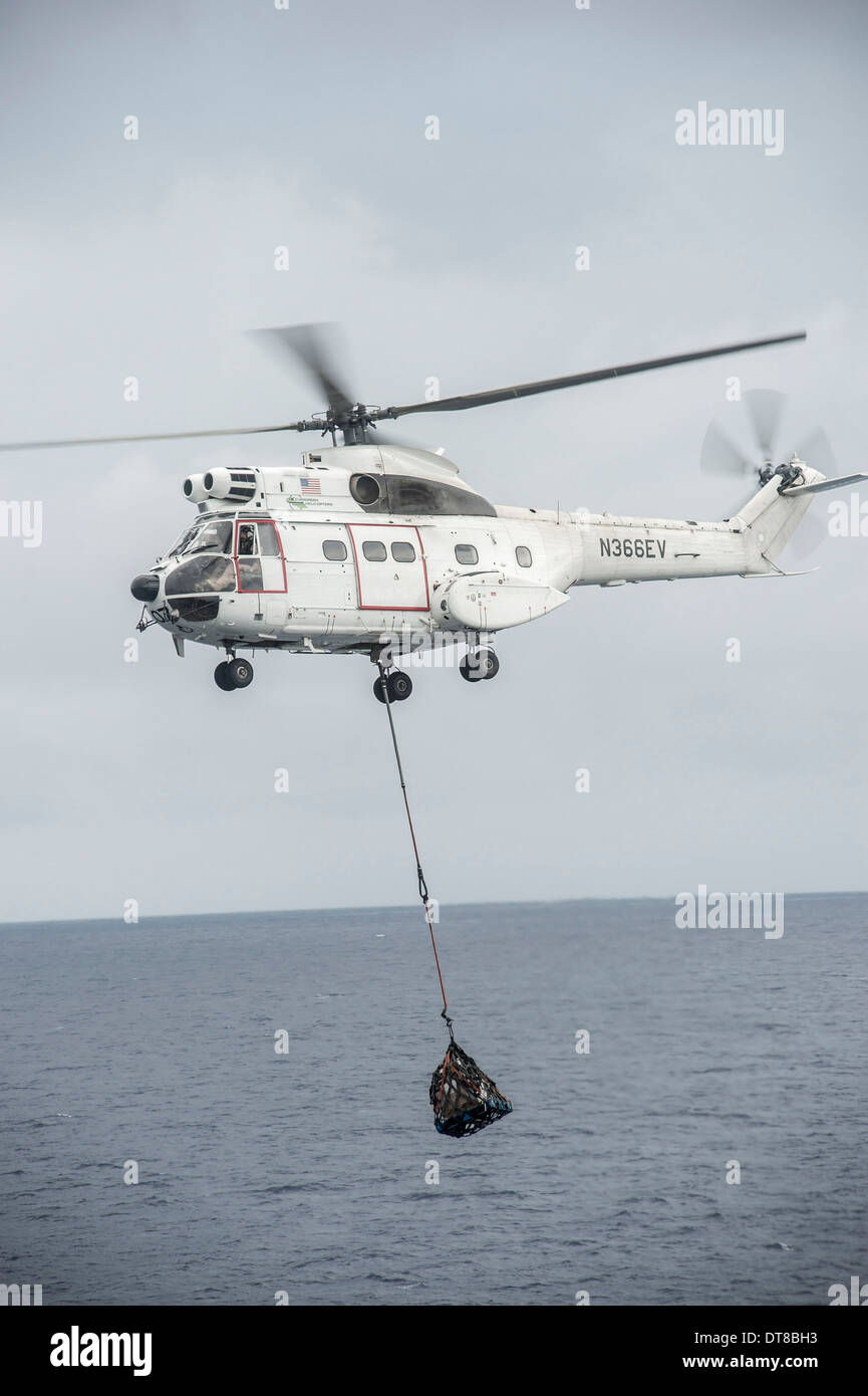 An SA-330 Puma transport helicopter moves cargo during a vertical replenishment. - Stock Image