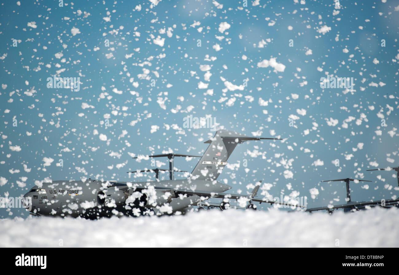 A C-17 Globemaster III on the flight line as fire retardant foam is released. - Stock Image