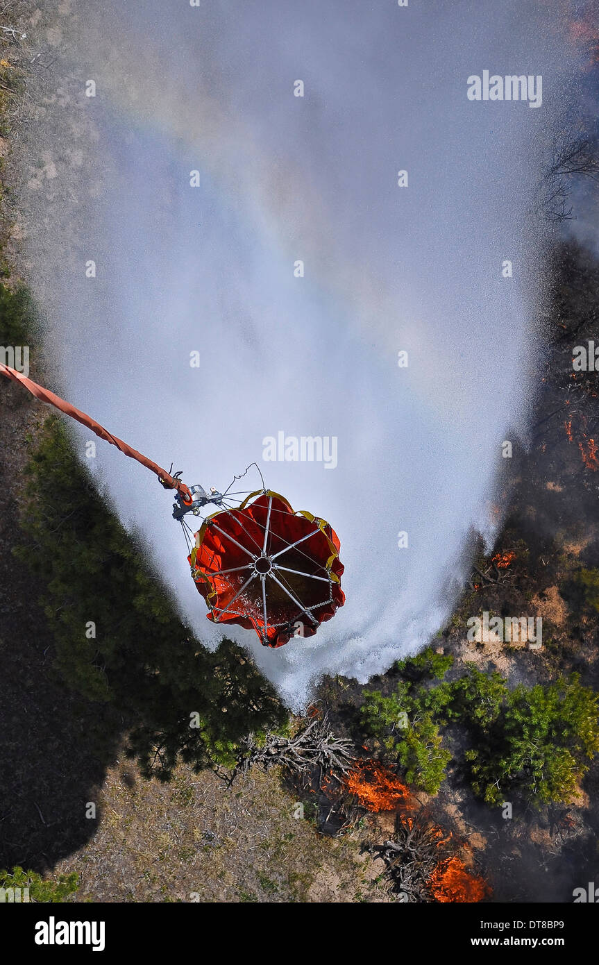 UH-60 Black Hawk helicopters perform water drops using Bambi Buckets. - Stock Image