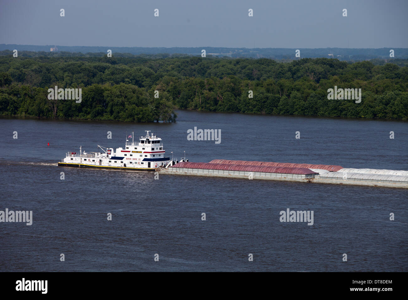 A barge slowly heads south on the Mississippi River at Burlington, Iowa. - Stock Image