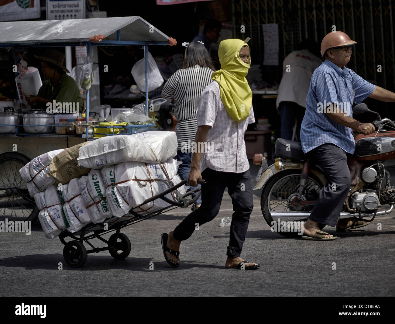 Thailand street scene with man using a hand cart to deliver market goods. Thailand S. E. Asia - Stock Image