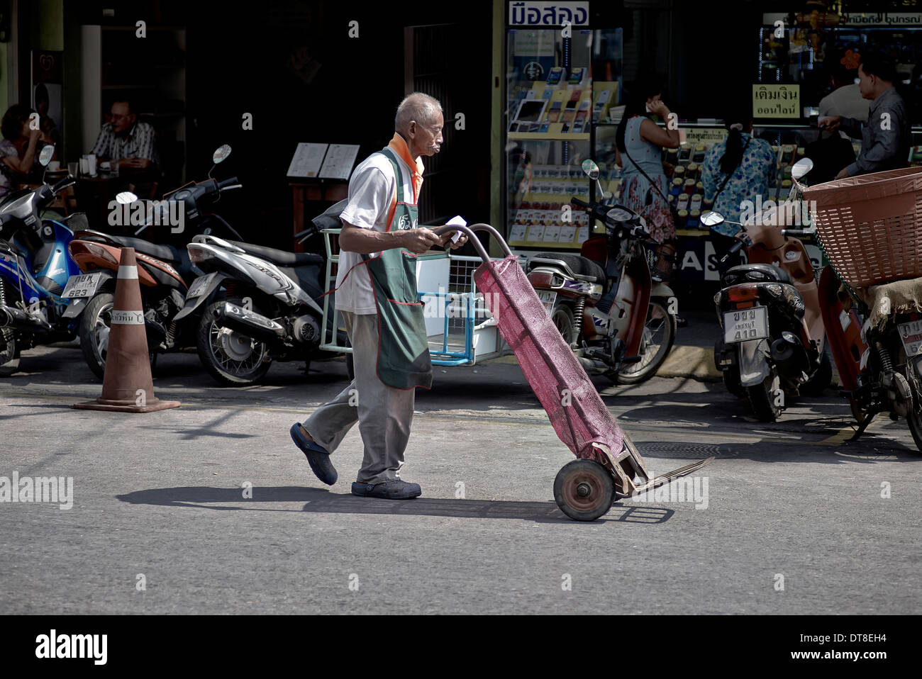 Thailand street scene with elderly man using a hand cart to deliver market goods. Thailand S. E. Asia - Stock Image