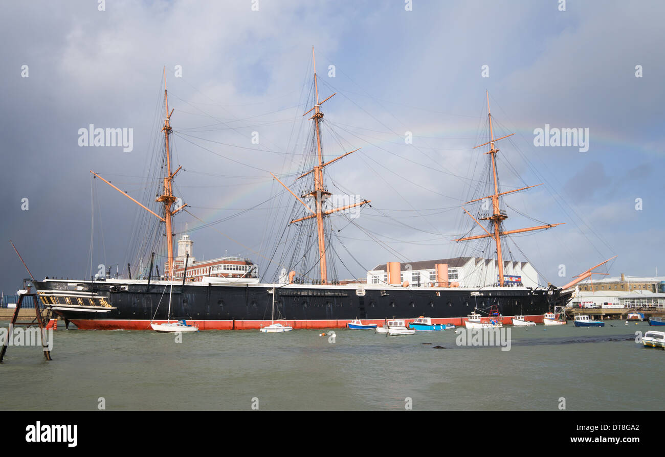Early British steam powered armour-plated, iron-hulled warship HMS Warrior, built 1860, with rainbow, Portsmouth England UK - Stock Image