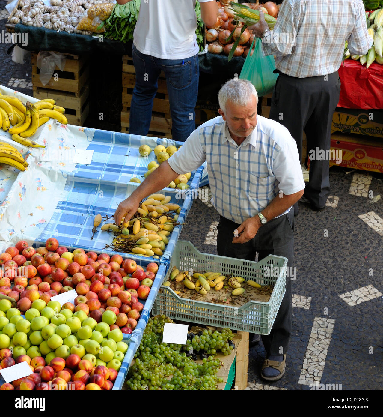 Funchal Madeira The indoor fruit and vegetable market Mercado dos Lavradores A market trader tidying his stall - Stock Image
