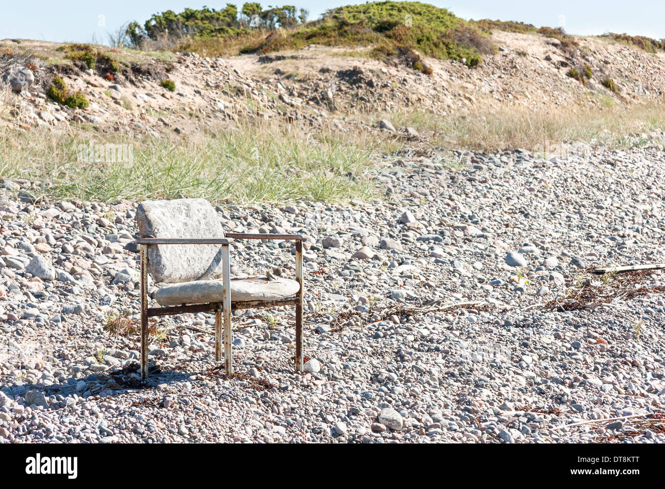 Old worn out chair outside on a land covered with small stones - Stock Image