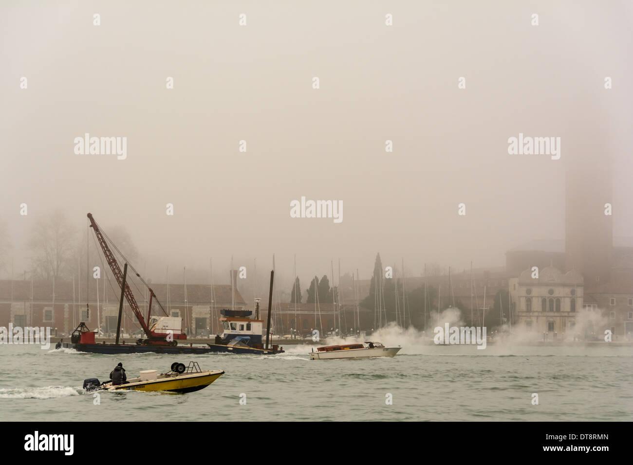 Venice, Italy. San Giorgio Maggiore island Campanile belltower covered in fog, boats and water traffic. Stock Photo