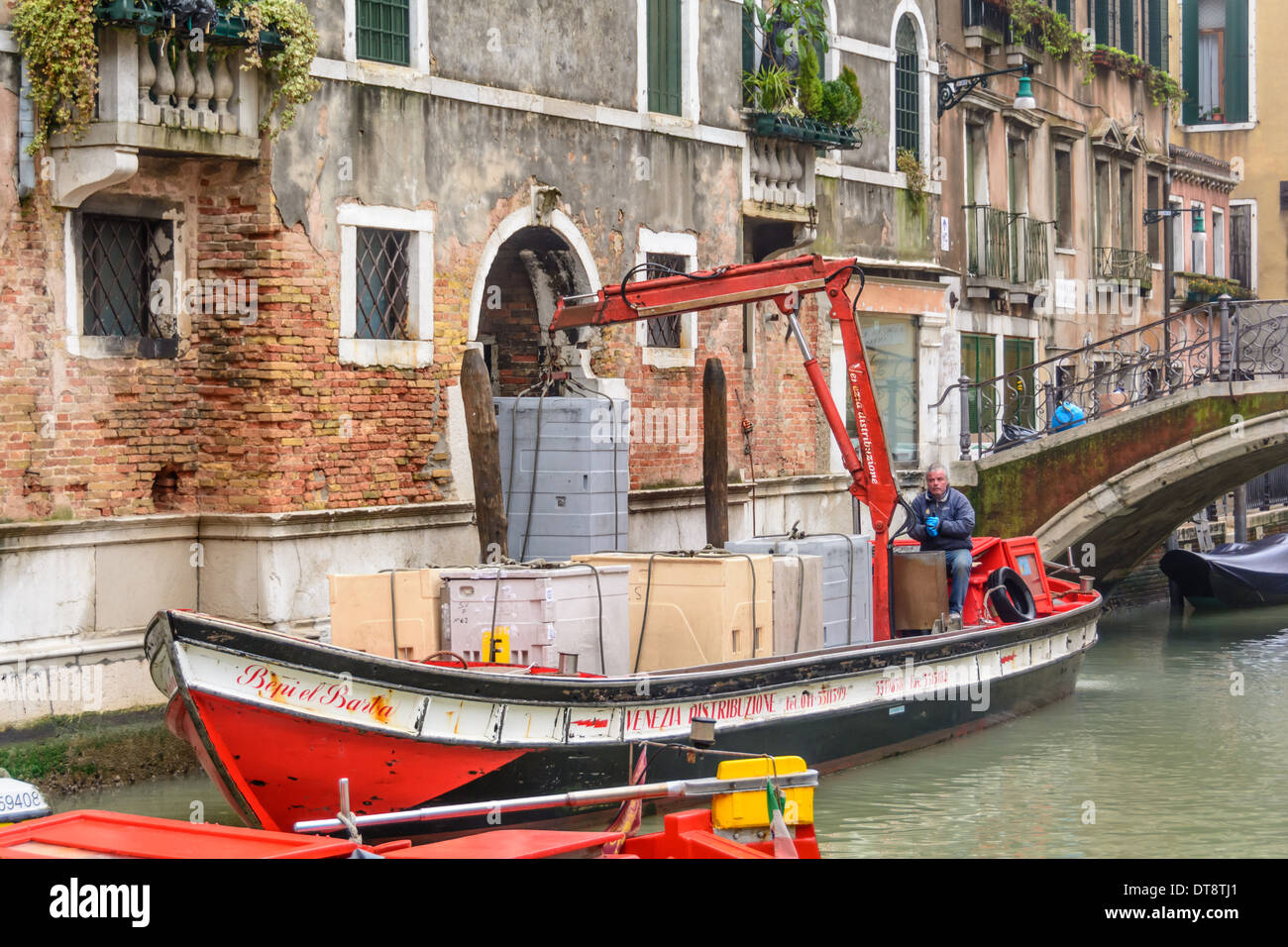 Venice, Italy. Freight-laden barge with mounted crane in a narrow Venetian canal unloading containers. Stock Photo