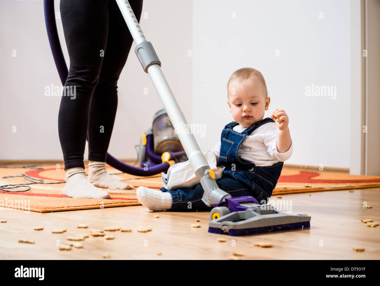 Cleaning up the room - woman with vacuum cleaner, baby sitting on floor - Stock Image