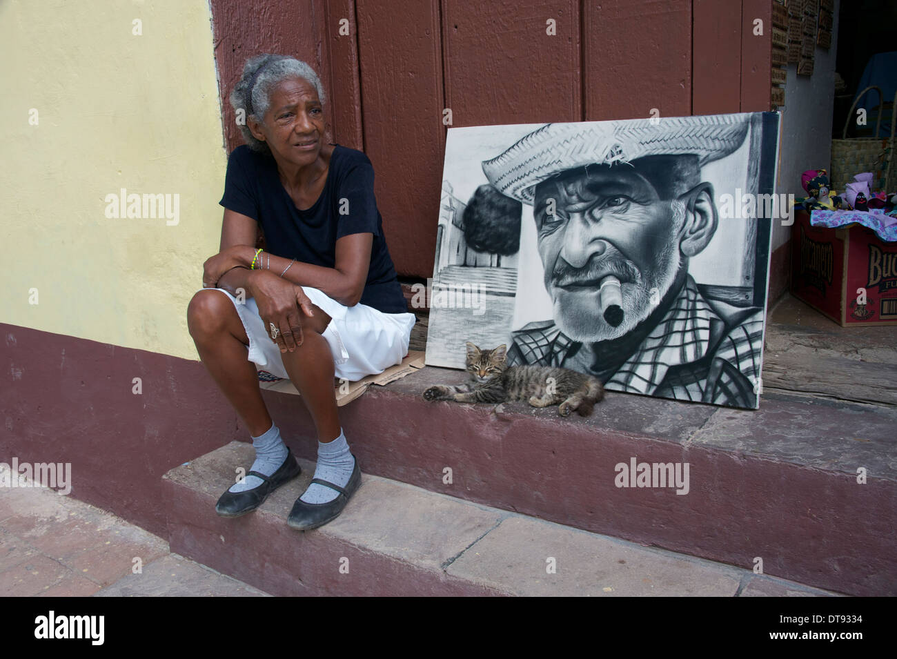 Woman with picture and kitten on step, Trinidad, Cuba - Stock Image