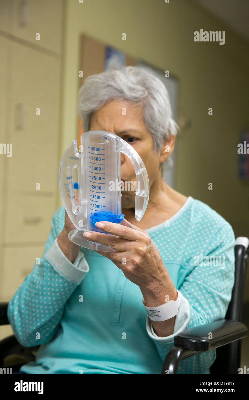 75 year old Hispanic senior citizen uses a medical breathing exercise apparatus while in a rehabilitation hospital in Texas. - Stock Image