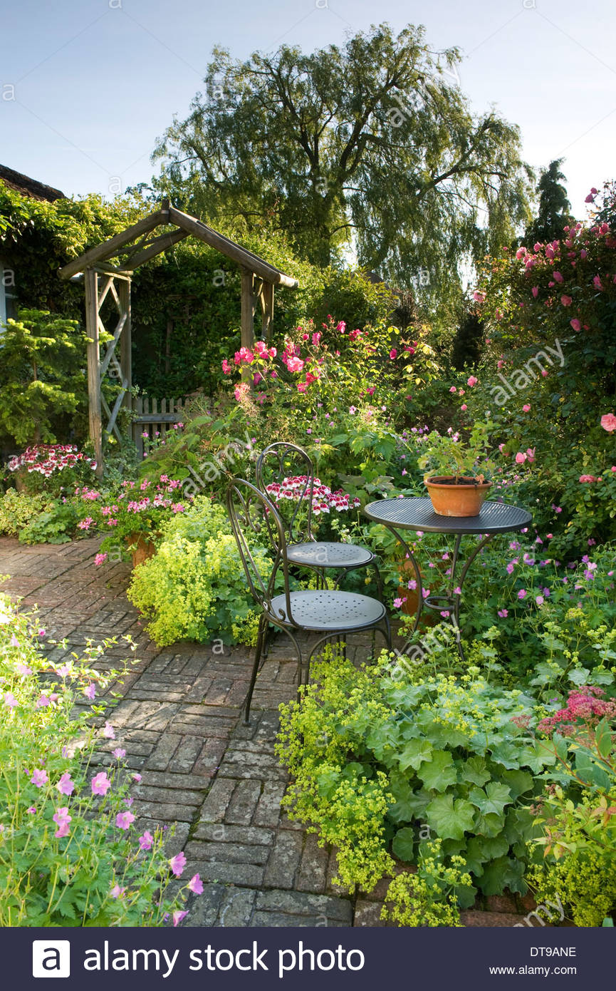 summer country patio with table and chairs rustic arch gate cottage garden summer  herringbone brick paving flowers - Stock Image
