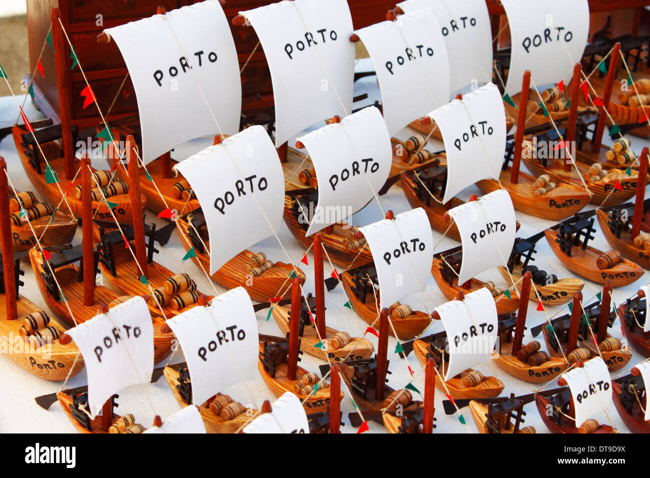 Souvenirs of Porto, many little wooden boat models with white sails that have Porto inscribed on them - Stock Image