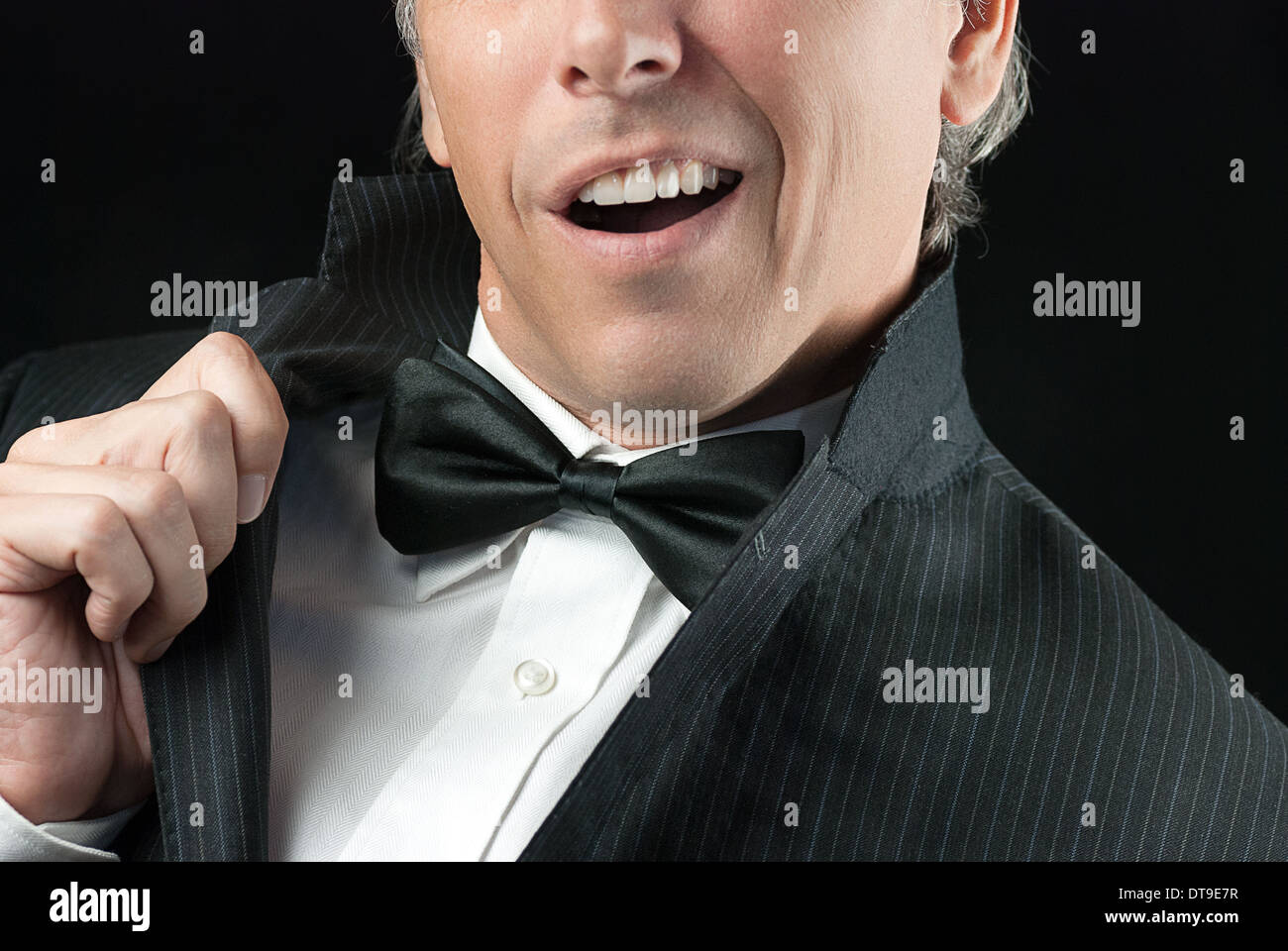 Close-up of a man in a tux doing an Elvis impression. - Stock Image