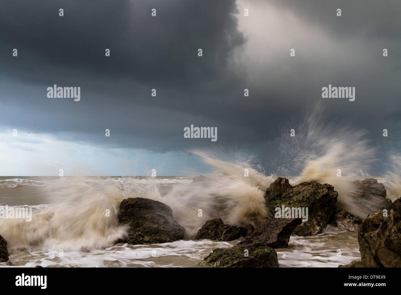 Waves crashing around rocks during a storm Stock Photo