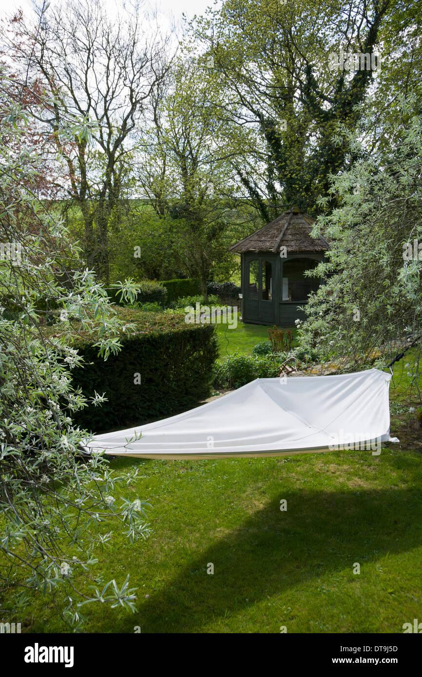 UK gardens. Contemporary garden hammock between two trees. - Stock Image