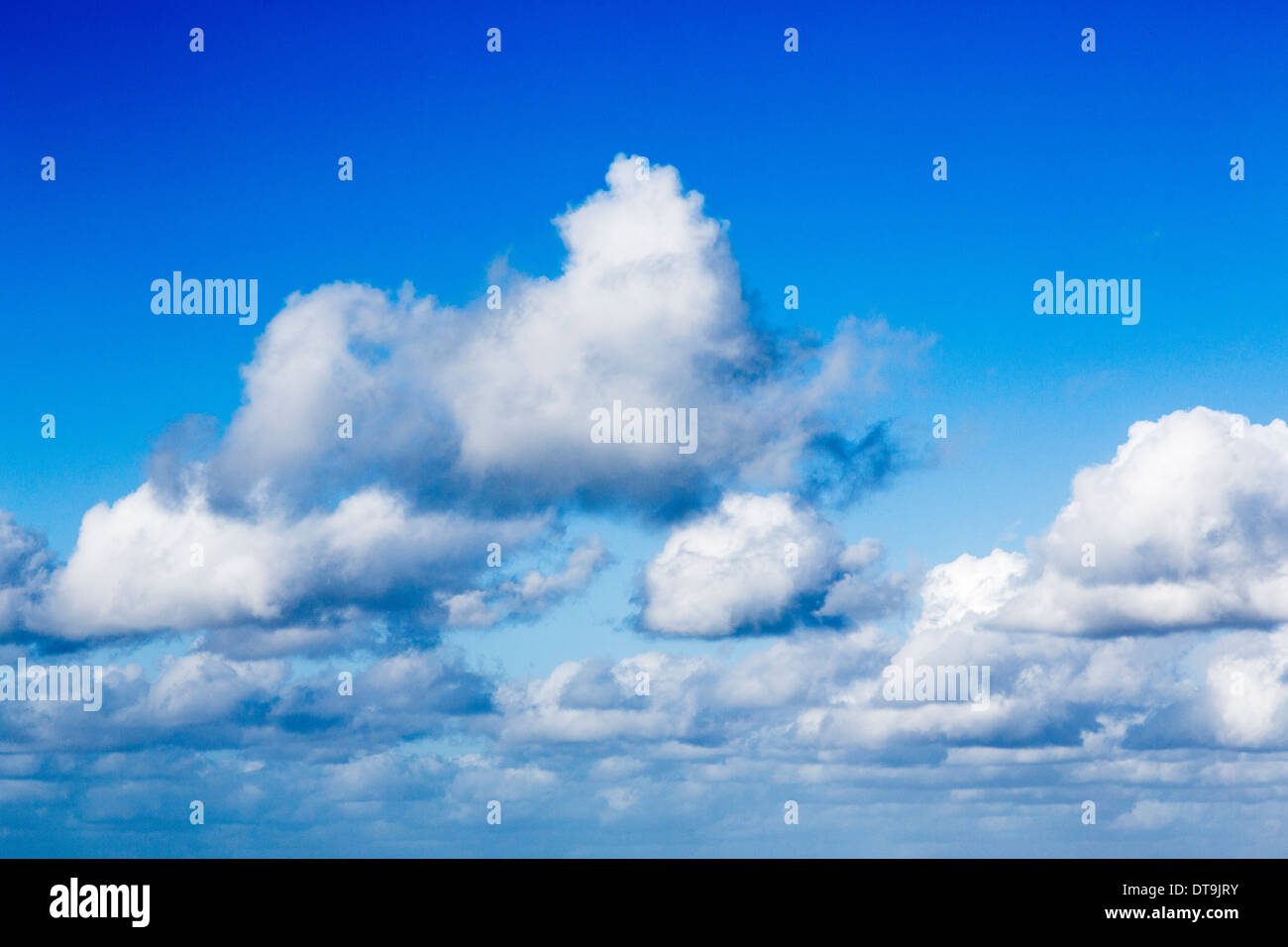 White fluffy cumulus clouds with flat bases in an azure blue sky over the south of England - Stock Image