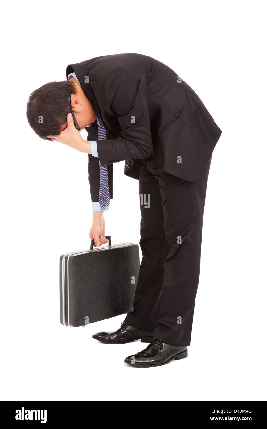 afflictive businessman stoop and hold his head in sutdio - Stock Image