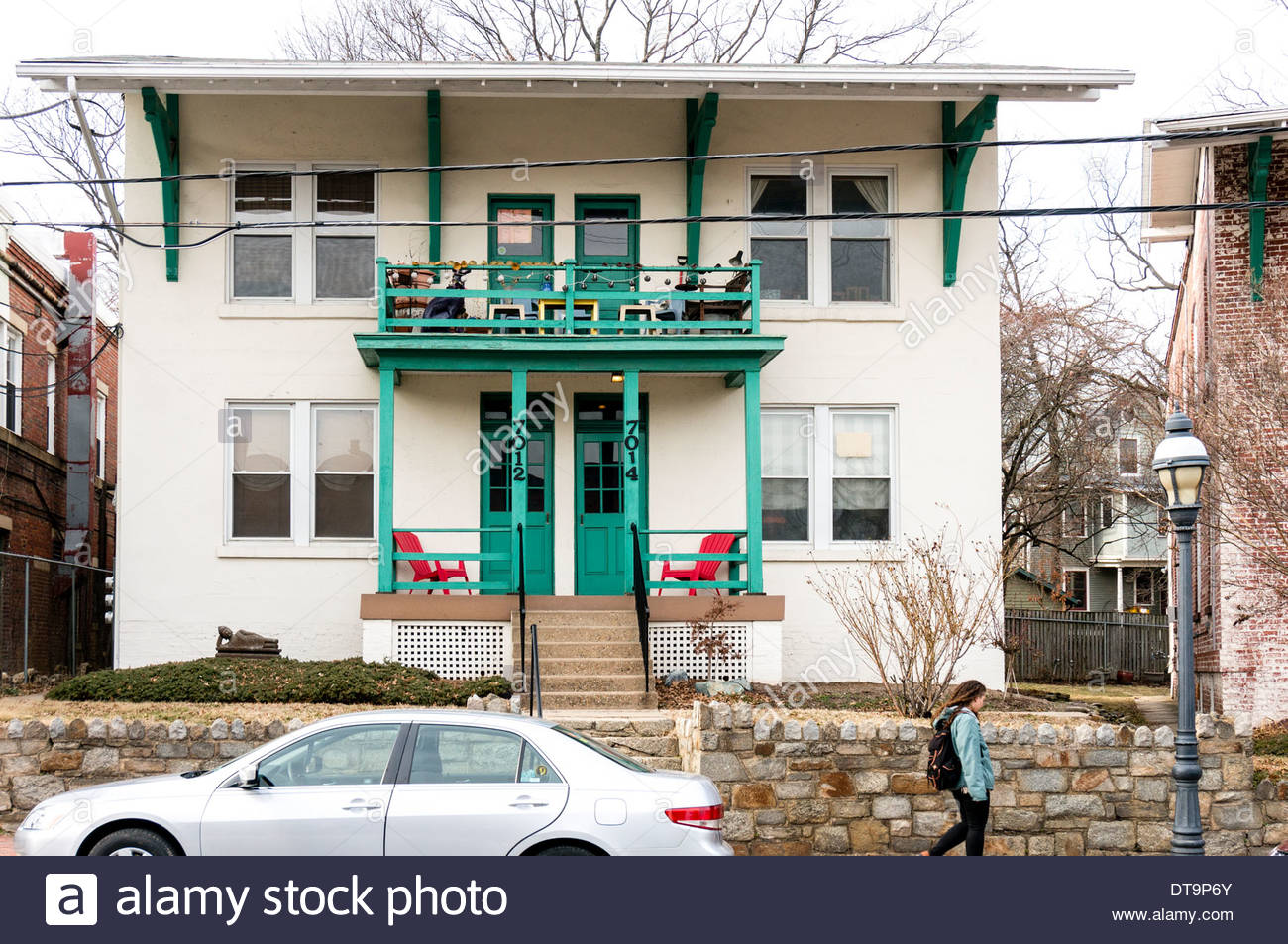 A young woman walks by a duplex house along Carroll Avenue in Takoma Park, Maryland - Stock Image