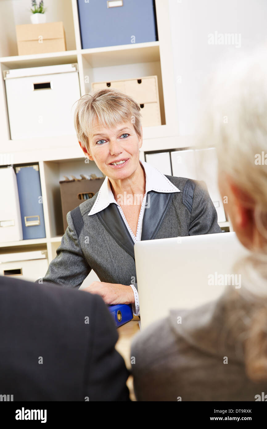 Elderly woman in bank talking to two senior customers about their finances - Stock Image