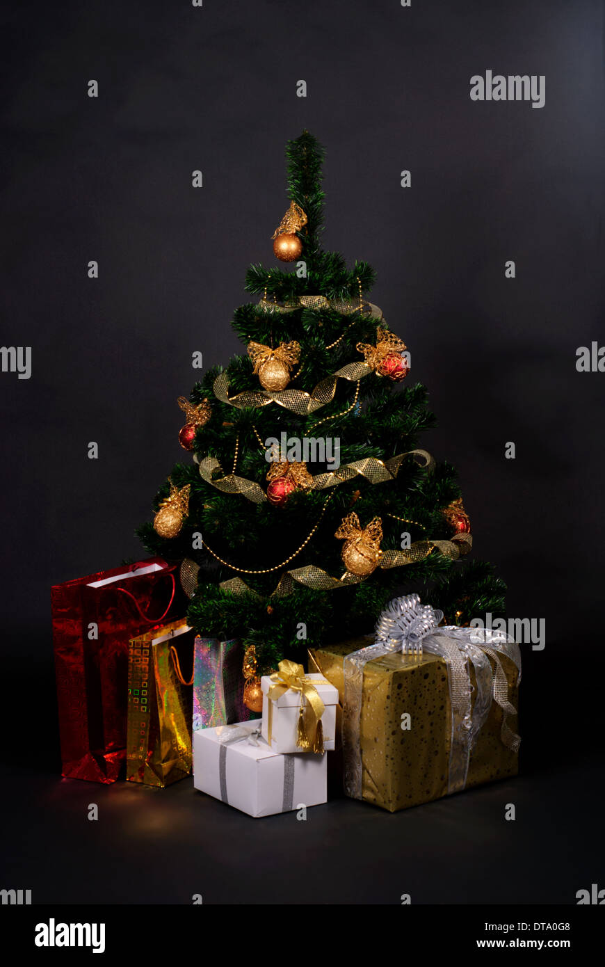 christmas tree with different gifts isolated on black Stock Photo
