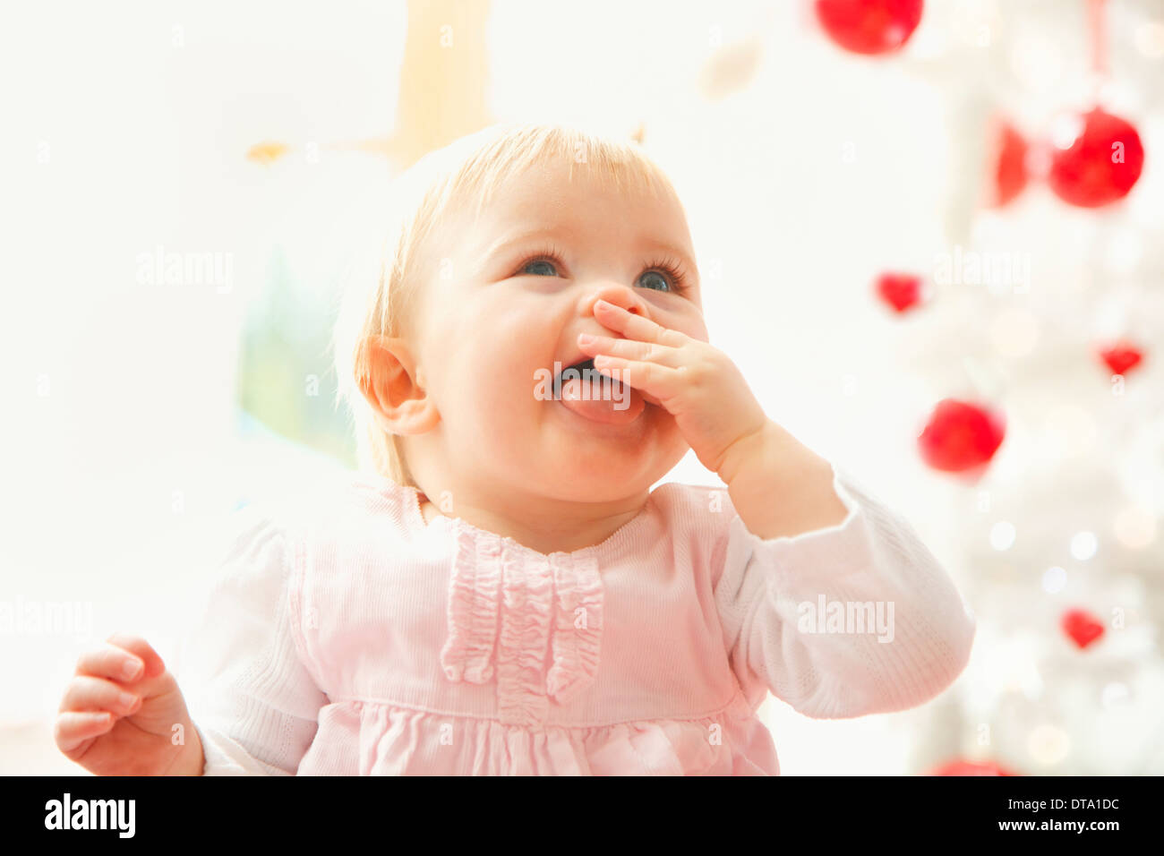 Portrait of Baby Girl with Finger in Mouth and Tongue Sticking Out Stock Photo