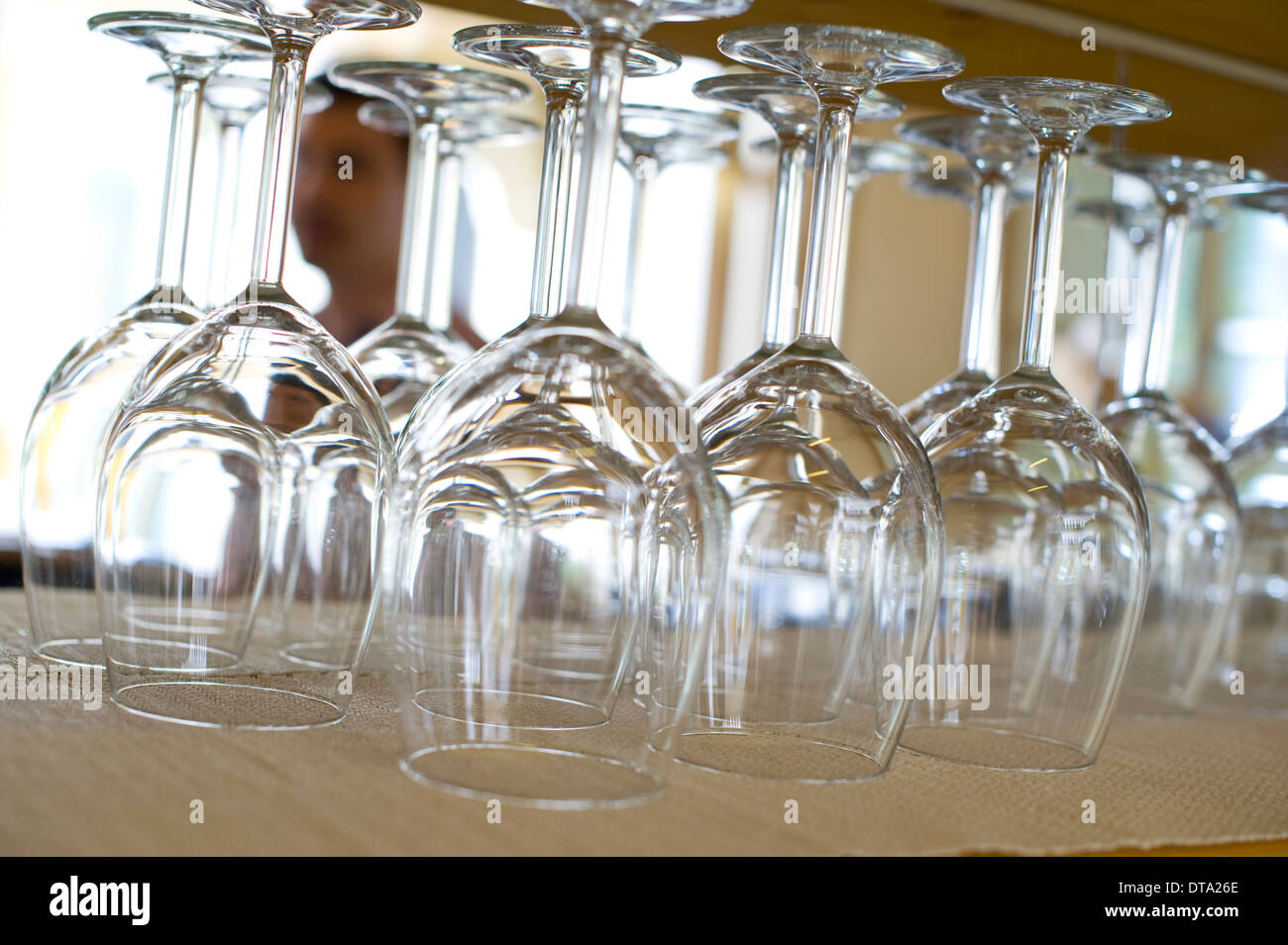 Upside down wine glasses in a restaurant - Stock Image