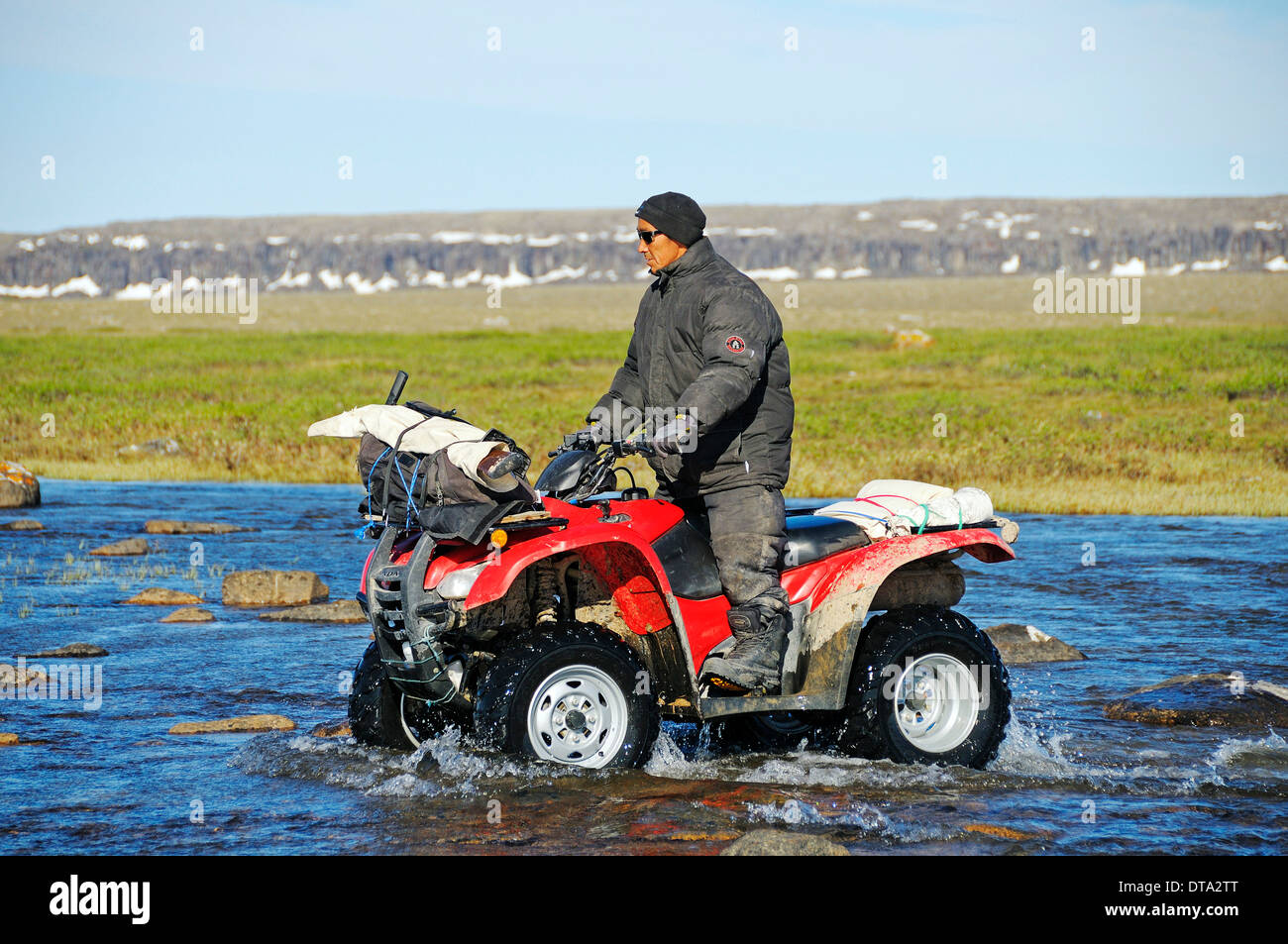 Man of the Inuit people riding a quad bike, ATV, through a river in the tundra on Victoria Island, formerly Holman Island - Stock Image