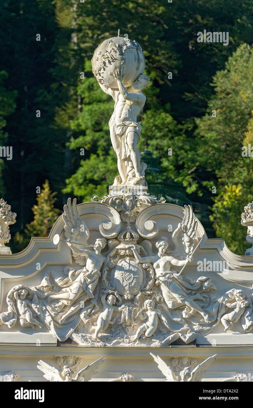 Statue of Atlas holding the celestial sphere, angels and putti around the Bavarian coat of arms on the pediment of Schloss - Stock Image
