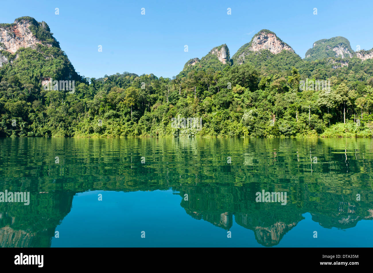 Forested karst limestone mountains with jungle vegetation reflected in the water, Rachabrapha reservoir, Chiao Lan Stock Photo