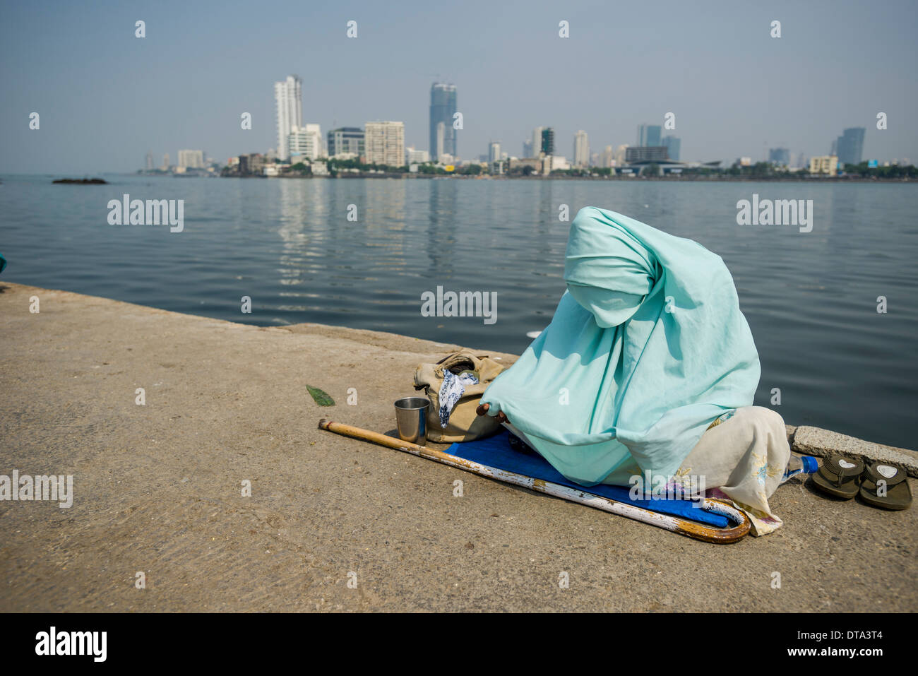 A Muslim woman wearing a burka is begging for money on the walkway, Mahalaksmi, Mumbai, Maharashtra, India - Stock Image