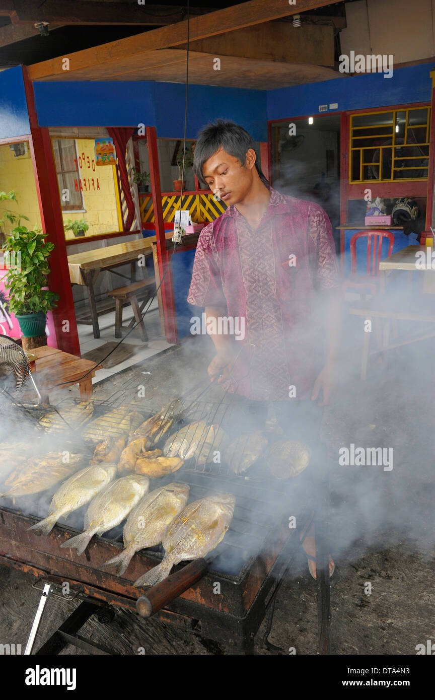 Javanese man grilling fish in a restaurant, Biak city, Biak Island, West Papua, Indonesia - Stock Image