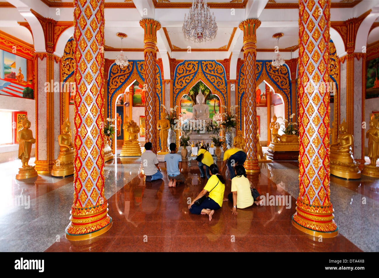 Visitors praying in front of the altar, columns, Wat Chalong temple, Phuket, Thailand - Stock Image