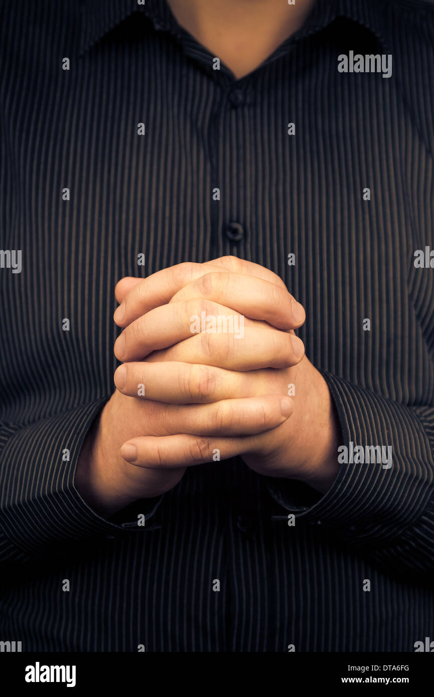 A man wearing a shirt with folded hands - Stock Image