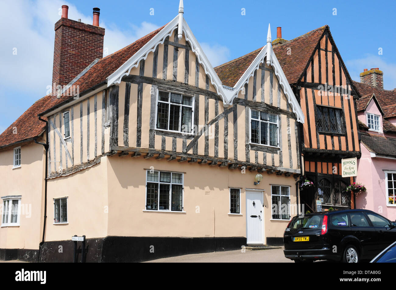 Medieval timberframed houses and 21st century cars in the High Street, Lavenham. - Stock Image