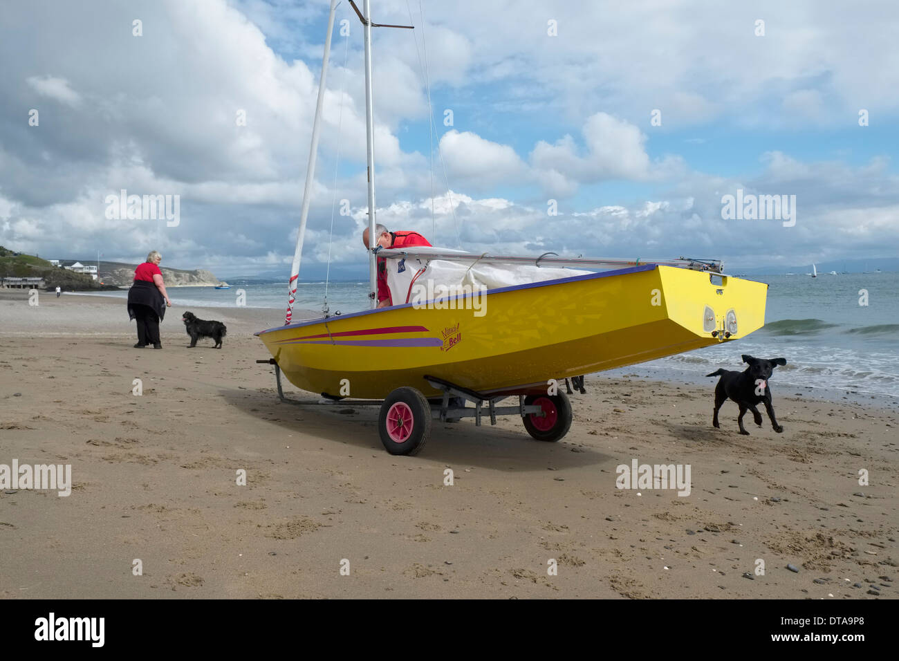 After the aftrenoon sail : Removing the mainsail from a modern yellow hulled dinghy on the beach at Abersoch, North Wales - Stock Image