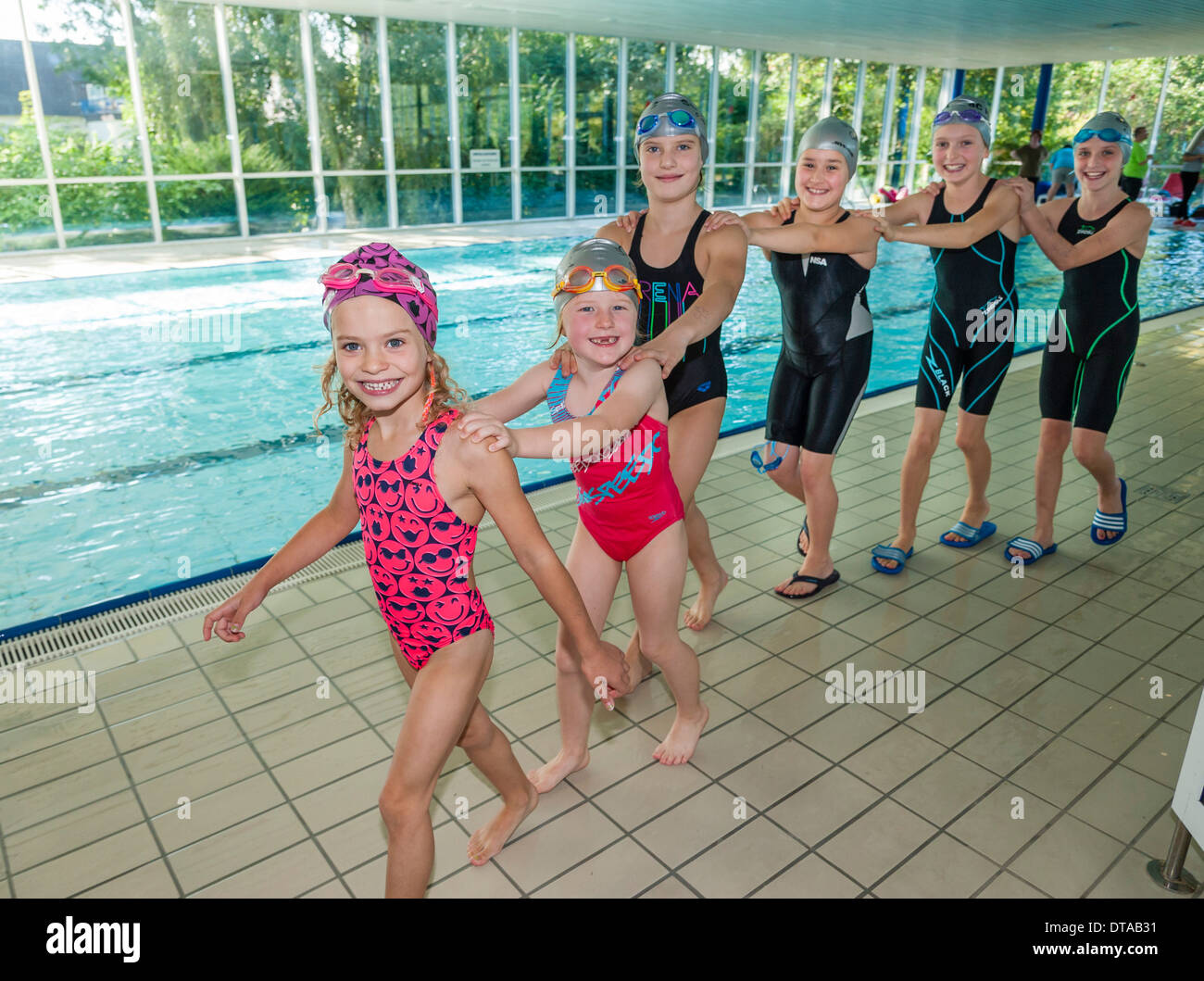 Young swimmers enjoy a polonaise at the pool during a pause in their swimming competition. - Stock Image