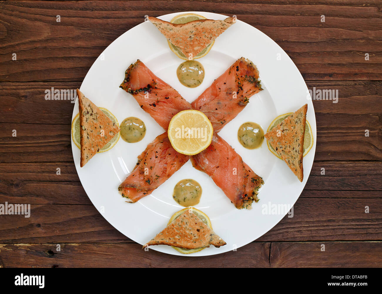 Smoked salmon starter arranged on a plate with a table top background - Stock Image