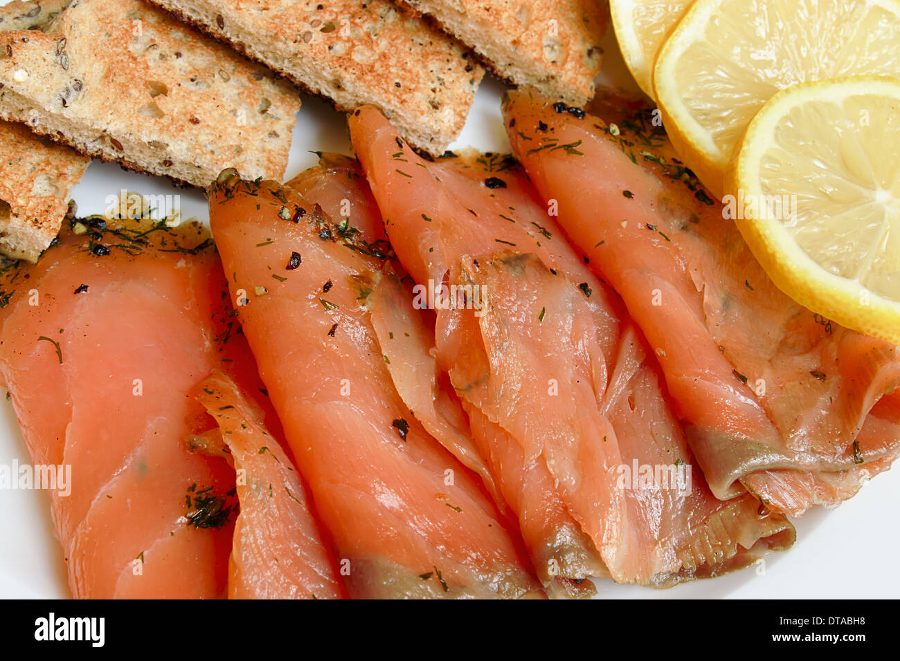 Smoked salmon sliced and arranged with toast a popular appetizer - Stock Image