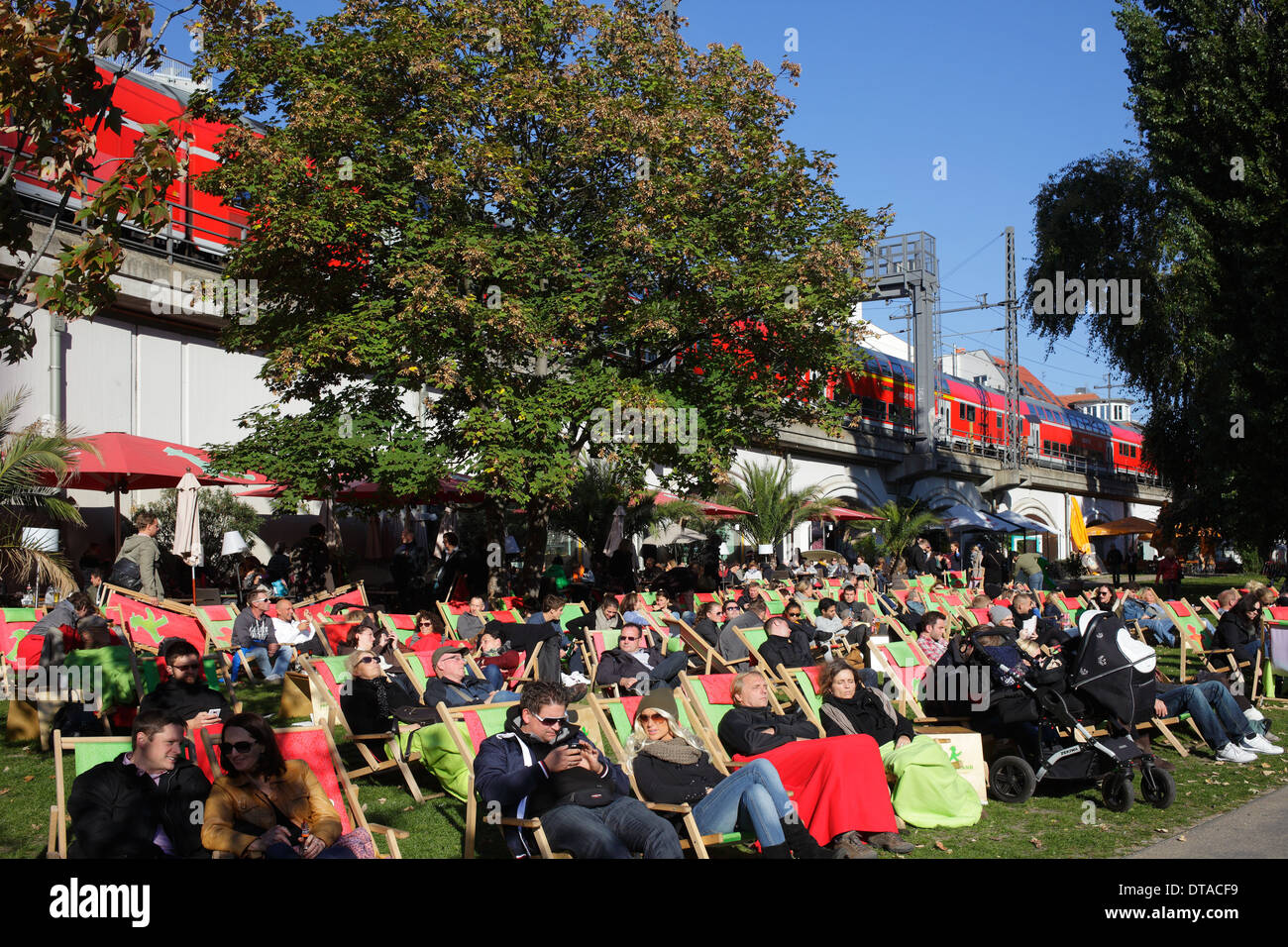 Berlin, Germany, guests basking in deckchairs on the light rail line - Stock Image