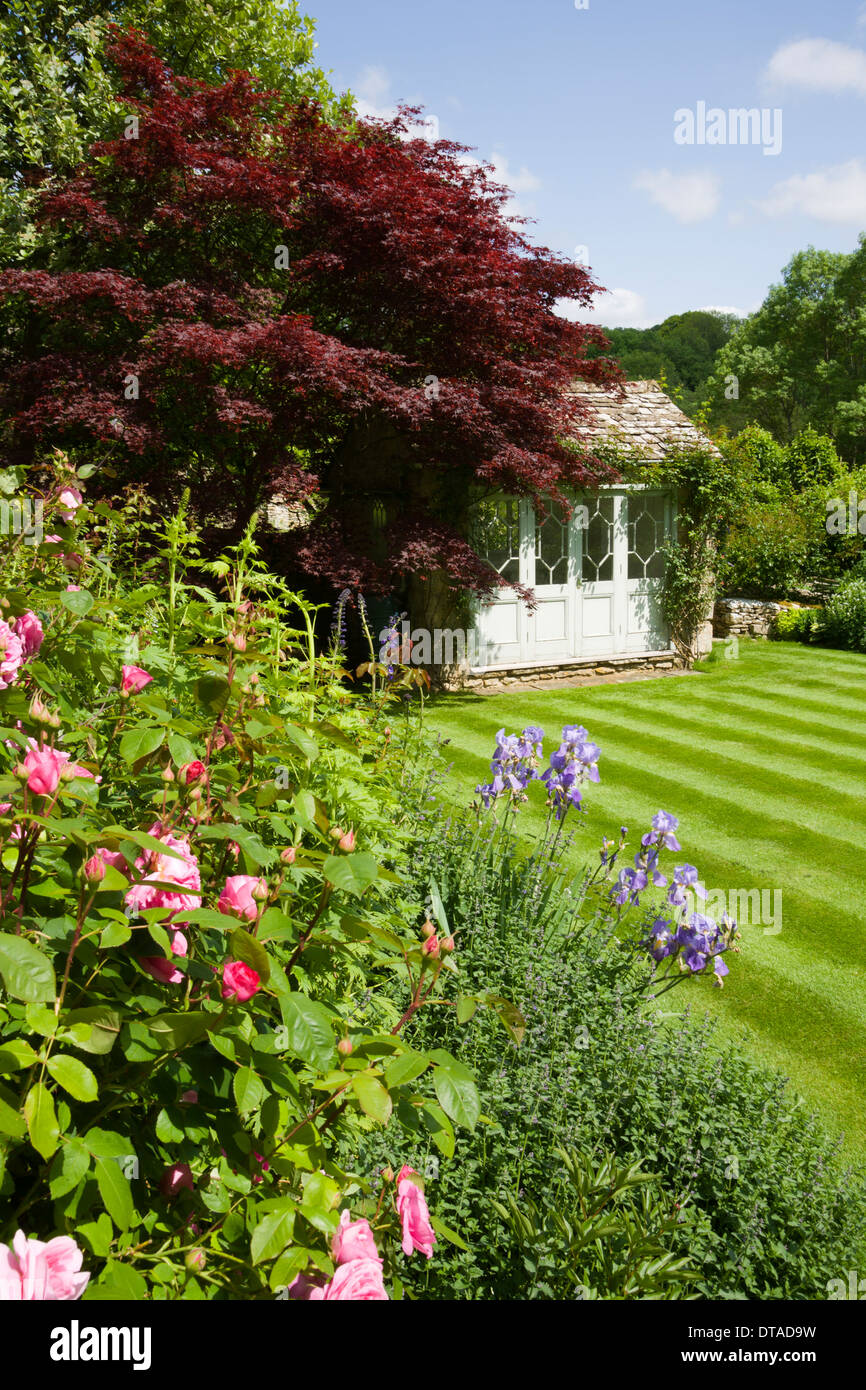 UK gardens. Summer flowerbed striped lawn and a period summerhouse. - Stock Image