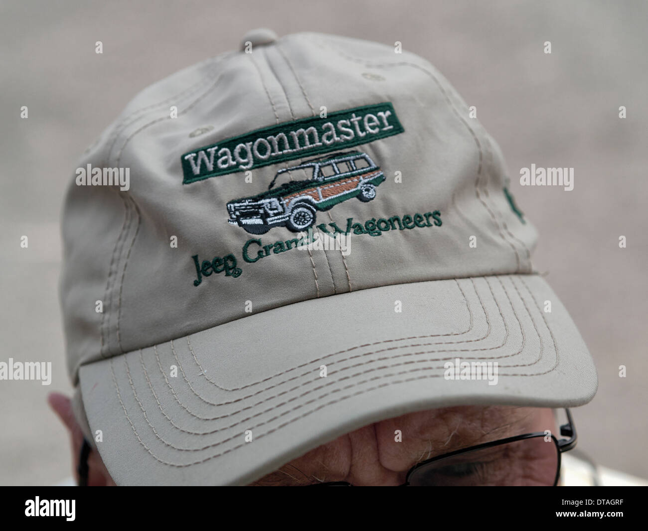 004e45bcecf Man wearing a baseball cap embroidered Jeep Grand Wagoneers. Vehicle  advertising material