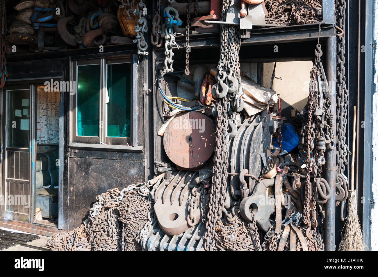 Chains and various tools hanging in a workshop. - Stock Image
