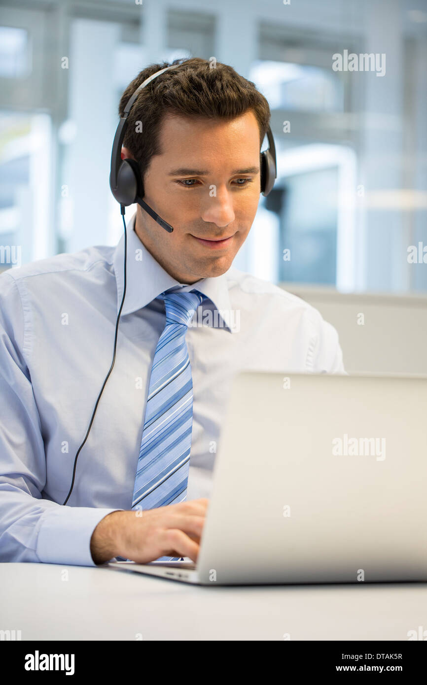 Businessman in office on phone with headset, hotline Stock Photo